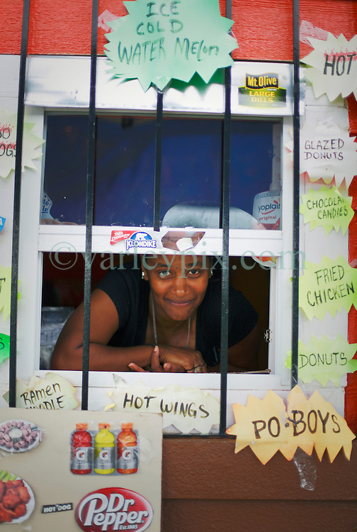 27 August 2014. Lower 9th Ward, New Orleans, Louisiana.<br /> Hurricane Katrina 9 years later. Keisha Cotlon peers from the window of the first grocery store set to return to the Lower 9th Ward.  The building is being renovated and will be officially opened on September 9th as the area struggles to recover from Hurricane Katrina.<br /> Photo; Charlie Varley/varleypix.com