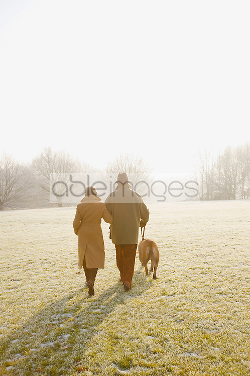 Back view of a mature couple walking with a dog on a frosty park