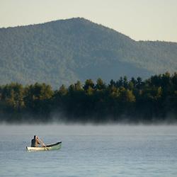 A paddler canoeing on Umbagog Lake near the Umbagog Lake State Campground in Errol, NH.  Early morning.