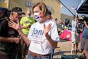 10 OCTOBER 2020 - DES MOINES, IOWA: Iowa Governor KIM REYNOLDS talks to supporters at a campaign event for Sen Joni Ernst. Sen. Ernst left Sioux City Saturday morning and stopped in Carroll, IA, before ending the day's ride in Des Moines at Big Barn Harley-Davidson. She had a rally in the parking lot of Harley-Davidson dealership. The ride is a fundraiser for the Puppy Jake Foundation (which provides service animals to veterans) and the Greater Cedar Rapids Community Foundation's Derecho Disaster Recovery. About 50 people rode with Sen Ernst from Carroll to Des Moines and another 80 were waiting for her in Des Moines.     PHOTO BY JACK KURTZ