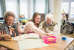 Senior women with girl doing craft activity at rest home