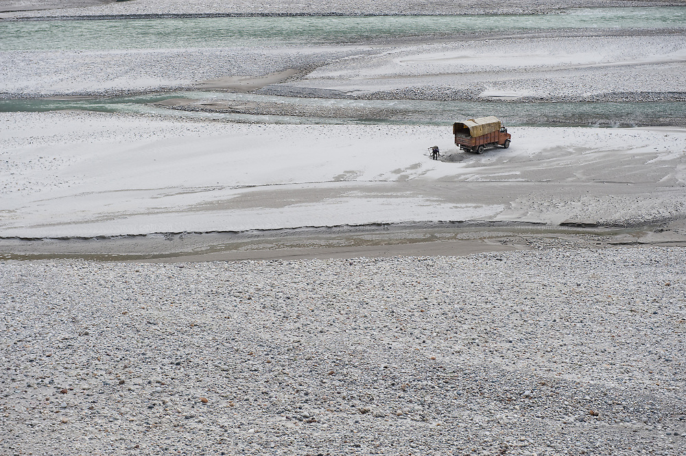 People load a truck with sand from a river bed in the high Himalaya mountains, September 2009