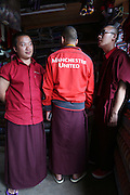 Buddhist monks supporter of Manchester United Football Club, plus they are team colours they can wear. Paro town centre, Bhutan..Bhutan the country that prides itself on the development of 'Gross National Happiness' rather than GNP. This attitude pervades education, government, proclamations by royalty and politicians alike, and in the daily life of Bhutanese people. Strong adherence and respect for a royal family and Buddhism, mean the people generally follow what they are told and taught. There are of course contradictions between the modern and tradional world more often seen in urban rather than rural contexts. Phallic images of huge penises adorn the traditional homes, surrounded by animal spirits; Gross National Penis. Slow development, and fending off the modern world, television only introduced ten years ago, the lack of intrusive tourism, as tourists need to pay a daily minimum entry of $250, ecotourism for the rich, leaves a relatively unworldly populace, but with very high literacy, good health service and payments to peasants to not kill wild animals, or misuse forest, enables sustainable development and protects the country's natural heritage. Whilst various hydro-electric schemes, cash crops including apples, pull in import revenue, and Bhutan is helped with aid from the international community. Its population is only a meagre 700,000. Indian and Nepalese workers carry out the menial road and construction work.