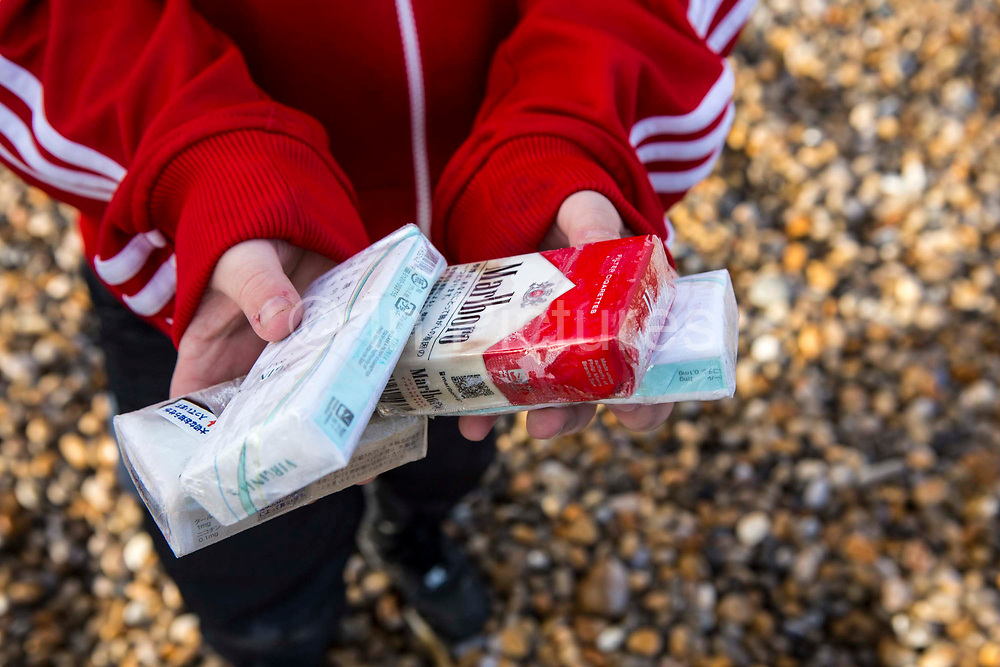 A person holds a packet of wet cigarettes in their hand. The cigarette packets have been washed up on Chesil Beach from a cargo container ship accident on Jurassic Coast of Dorset, UK.