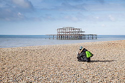 A woman sitting on the beach at Brighton.