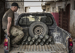 October 30, 2016 - Bakhdida, Nineveh Governorate, Iraq -  A man sits in the back of a pickup truck with mortar slugs from ISIS that were found in Al Hamdaniyah. (Credit Image: © Berci Feher via ZUMA Wire)