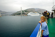 Child (9 years old) at railing of large ship in early morning light, with Cruise Liner and the Franjo Tudjman Bridge (Most Franja Tudjmana) in background. Dubrovnik, Croatia