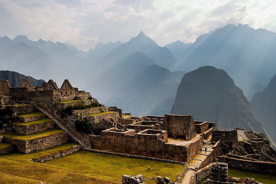 Two visitors are dwarfed by the ruins of Machu Picchu, an ancient Inca site perched above the Urubamba Valley in Peru, as morning light filters through the clouds on September 21, 2005.