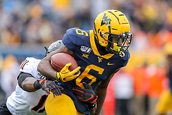 Nov 23, 2019; Morgantown, WV, USA; West Virginia Mountaineers running back Kennedy McKoy (6) runs the ball during the second quarter against the Oklahoma State Cowboys at Mountaineer Field at Milan Puskar Stadium. Mandatory Credit: Ben Queen-USA TODAY Sports