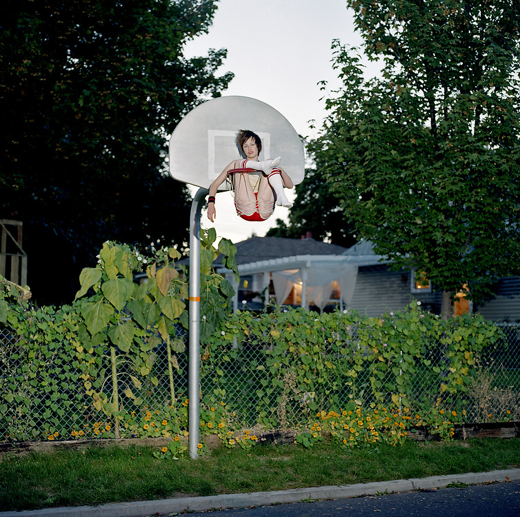 Young woman sitting in a basketball hoop on a residential street early evening.