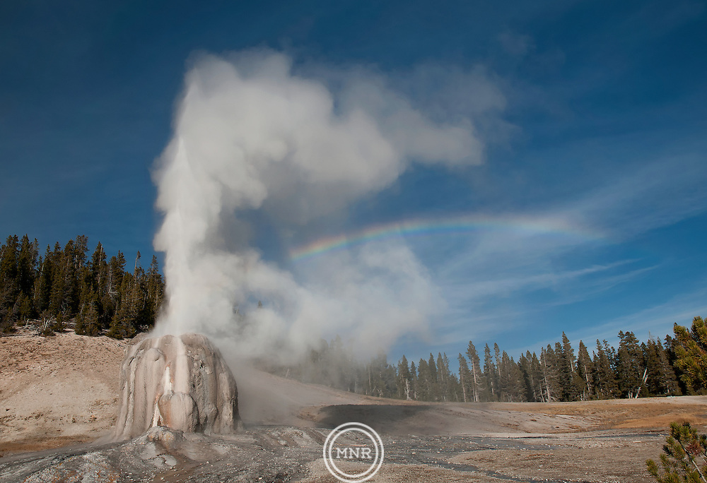 Lone Star Geyser erupts with the late afternoon sun creating a Rainbow through the steam.