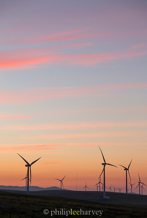 Wind turbines on hill at sunset with moody sky in background, Tarifa, Andalusia, Spain