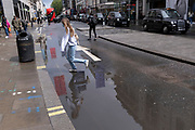 A young woman runs through a puddle left by seasonal Spring rainfall on Oxford Street, on 24th May 2021, in London, England.