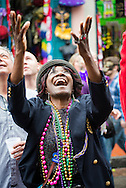 A woman raises her arms and laughs while looking up toward a balcony on Bourbon Street during Mardi Gras 2013.