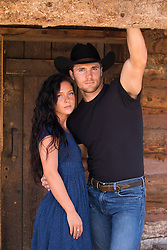 sexy cowboy and his girl outdoors by a cabin