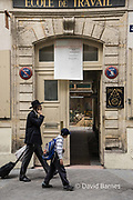 France, Paris, Jewish man and boy looking in while walking passed a trade school.