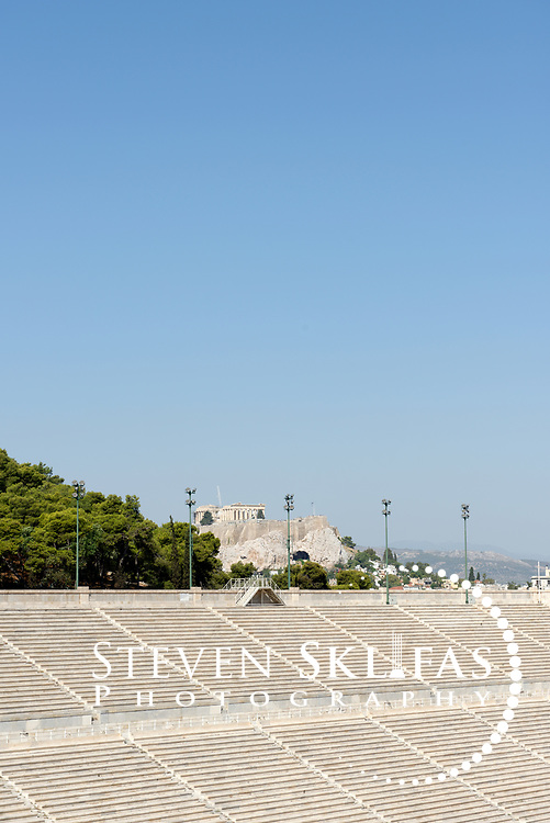 Athens. Greece.  View of the Acropolis from grandstand of the stadium. The Panathenaic (Kallimarmaro) stadium was used for the first international Olympic games of the modern era in 1896.  The completely marble stadium occupies the exact site of the original, built in 330BC which was used for the ancient Panathenaic games (part of the larger religious festival, the Panathenaia).