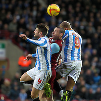 Burnley's David Jones battles with  Huddersfield Town's James Vaughan and Oliver Norwood<br /><br />Photo by Mick Walker/CameraSport<br /><br />Football - The Football League Sky Bet Championship - Huddersfield Town v Burnley - Saturday 30th November 2013 - The John Smith's Stadium - Huddersfield<br /><br />© CameraSport - 43 Linden Ave. Countesthorpe. Leicester. England. LE8 5PG - Tel: +44 (0) 116 277 4147 - admin@camerasport.com - www.camerasport.com
