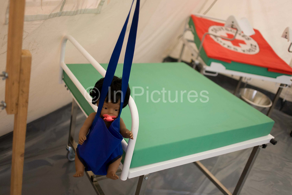 Maternity tent mock-up in emergency supplies warehouse, Deutsches Rotes Kreuz (DRK - German Red Cross) at their logistics centre at Berlin-Schönefeld airport. Ready for immediate loading into disaster zones, the equipment is stored near to where freight aircraft can fly anywhere in the world. The International Red Cross and Red Crescent Movement, with its 187 National Societies, is the world's largest humanitarian network. The German Red Cross is part of this universal community, which started 150 years ago to deliver comprehensive aid to people affected by conflict, disaster, sanitary emergencies, or social hardship, guided solely by their needs. Around four million volunteers and members support the Red Cross in Germany alone.