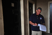Raul Moreno of the Dallas Police Department takes notes as he goes door to door as a part of the new 10/70/20 program at The Lodge at Timberglen apartments in Dallas on Saturday, March 30, 2013. (Cooper Neill/The Dallas Morning News)