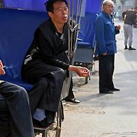 Asia, China, Beijing. Rickshaw drivers take a smoking break between pedaling tourists through Beijing's hutongs.