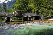 A family look at the view of the Savica river at Ucanc from a wooden bridge near Lake Bohinj, on 19th June, in Lake Bohinj, Sovenia.
