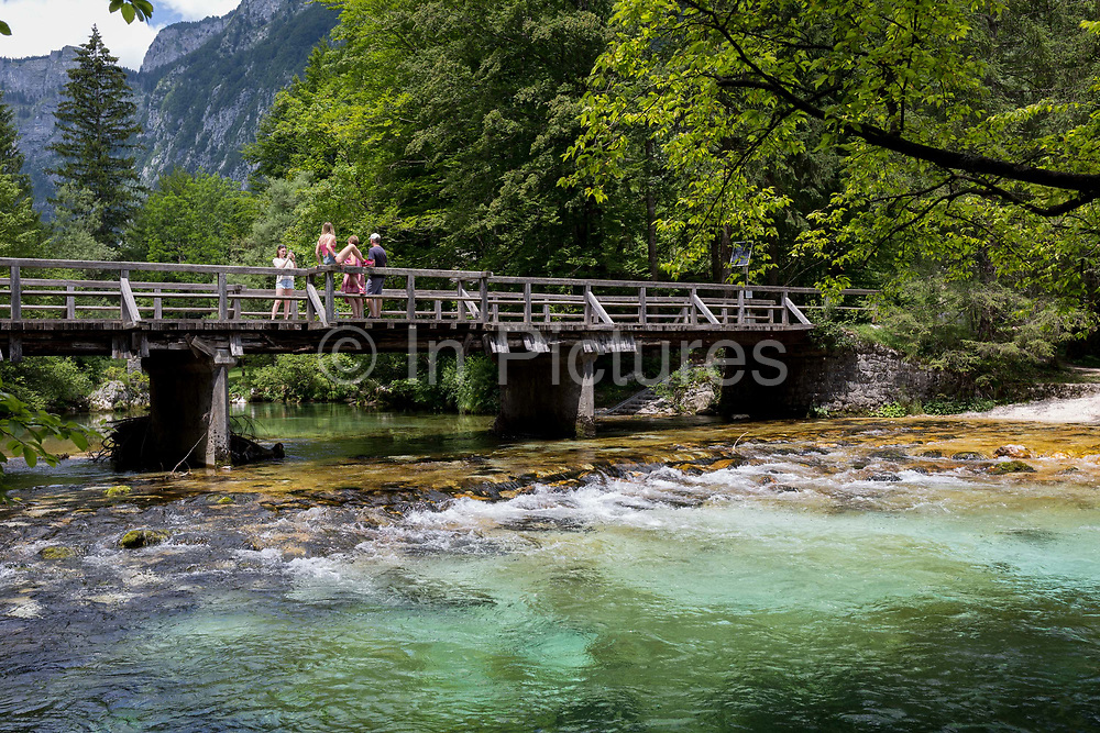 A family look at the view of the Savica river at Ucanc from a wooden bridge near Lake Bohinj, on 19th June, in Lake Bohinj, Sovenia.