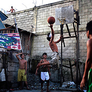 Youths play basketball in a small area in the Parola district of Tondo, Manila, the Philippines, one of the worst slum areas of Manila on October 8, 2008 in Manila, the Philippines. Photo Tim Clayton