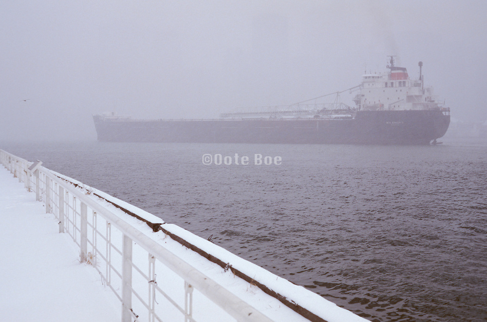 large cargo ship moving in the fog