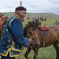 A father tends to his family's horses after his children rode  bareback in a 20km race at a traditional naadam festival on a remote pass in Arbulag Sum, near Muren in Hovsgol Aimag, Mongolia.  Motorcycles are a sign of changing times.