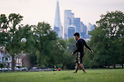 With the Shard and the capital's financial district in the distance, a young man kicks a football towards an unseen opponent in Ruskin Park, on 7th June 2021, in south London, England.