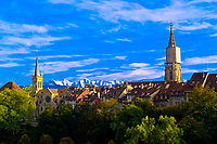 The Church of Saints Peter and Paul (left) and the Munster (Cathedral of Bern)  on right in the medieval city center of Bern, with peaks of the Swiss Alps behind, Canton Bern, Switzerland