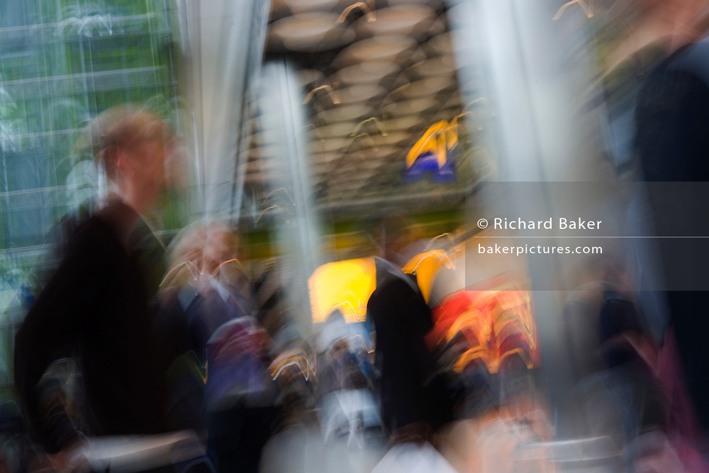 Blurred passsengers and relatives to show busy arrivals atmosphere on ground floor at Heathrow airport's Terminal 5