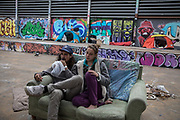 A couple from Sweden who has been living on the streets of Barcelona for 6 months, has settled during confinement in a square of the city center with a tent. They would like to be able to confine themselves to a shelter for homeless people, but they would be forced to be separated, he in a men's shelter and she in a women's one. So they prefer to sleep on the street together. Barcelona, March 27th. Photo by Eva Parey.<br /> <br /> Many homeless have been living in Barcelona for a while, sleeping on its streets, there are around 2,500 people, of different nationalities, ages and genders, but it is the quiet of the city - with hardly any passers-by -, in State of Alarm, that betrays their presence on the streets.<br /> The confinement order issued on March 15 cannot be applied to them. Their problem is twofold. Find a place to spend the day and avoid to be exposed to COVID disease19. Some have been able to occupy spaces in the city that before, being visible for the society, were prohibited. Others would like to occupy any of the places in the social shelters that the Barcelona City Council has specifically opened for them. More than fear of the disease, there are other fears. Loss of freedom seems the most precious asset for those who do not want to confine themselves in a closed space, in addition to protecting themselves from possible thefts or conflicts of all kinds. Behind each face there is a story. Some have been with this way of life for some time, but others, the cessation of many jobs or the closing of borders, have left them trapped in the street with no other option.