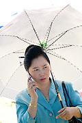 Elegant Hmong woman under white sun umbrella speaking on cell phone. Hmong Sports Festival McMurray Field St Paul Minnesota USA