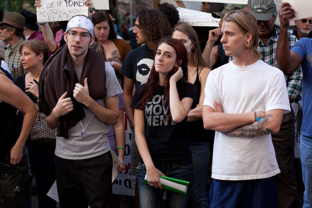 A young woman stands with her two friends as they received instructions on how to properly move the mass of people back to the Occupy camp.