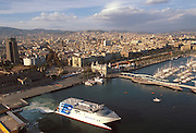 SPAIN, CATALONIA, BARCELONA Port Vell, the city's revitalized waterfront with the Colon Monument and Las Ramblas and the city skyline beyond