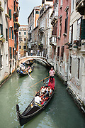 """Gondolas are traditional, flat-bottomed rowing boats which ferry people through Venetian canals. From a peak of 10,000 gondolas 200 years ago, just 500 gondolas now serve Venice. The banana-shaped modern gondola was developed in the 1800s. The left side of a gondola is made longer than the right side to resist leftwards drift at the forward stroke. The gondolier stands on the stern facing the bow and rows just on the right side, with a forward stroke and compensating backward stroke. The oar or rèmo is held in an oar lock, or fórcola, shaped for several rowing positions. The decorative fèrro (meaning iron) ornament on the front can be made of brass, stainless steel, or aluminum, as counterweight for the gondolier standing near the stern. The six horizontal lines and curved top of the ferro represent Venice's six sestieri (districts) and the Doge's cap. Painting gondolas black originated as a sumptuary law eliminating ostentatious competition between nobles. Until the early 1900s, many gondolas had a small cabin (felze) with windows which could be closed with louvered shutters—the original """"venetian blinds."""" The romantic """"City of Canals"""" stretches across 100+ small islands in the marshy Venetian Lagoon along the Adriatic Sea in northeast Italy, Europe. Venice and the Venetian Lagoons are honored on UNESCO's World Heritage List."""