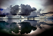 """Cumulus clouds are mirrored in the placid waters of Lake Murray, largest lake in Papua New Guinea, covering an area of some seven hundred square miles. About five thousand indigenous peoples inhabit this lake region. In 1923, the New York Times reported on an Australian expedition that used amphibious airplanes to chart Lake Murray and explorers' close encounters with indigenous pe<br />oples called, at the time, """"head hunters.""""  <br />© Steve Raymer / National Geographic Creative"""