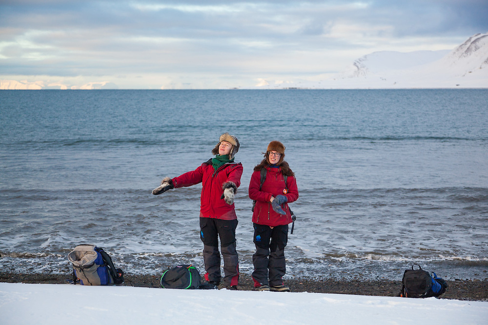 UNIS students Anine Hallander (left) and Heidi Lindebotten stand on the beach in Longyearbyen, Svalbard.