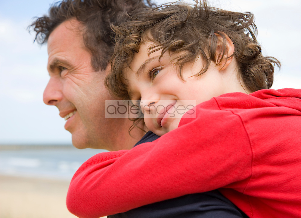 Close up of a young boy riding piggyback on his father shoulder