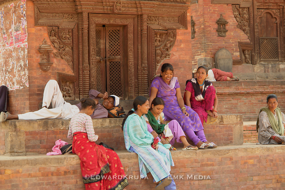 A group of colourfully dressed and happy looking local people get some respite from the scorching heat of the sun on steps of an anient Hindu temple in Patan, Durbar Square.  Listed by UNESCO world heritige site part of the Kathmandu Valley world heritige site in Nepal.
