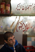 Men, some of whom have been protesting come back to the Cafe Tahrir to watch the scenes outside on a small television set, Cairo, Egypt