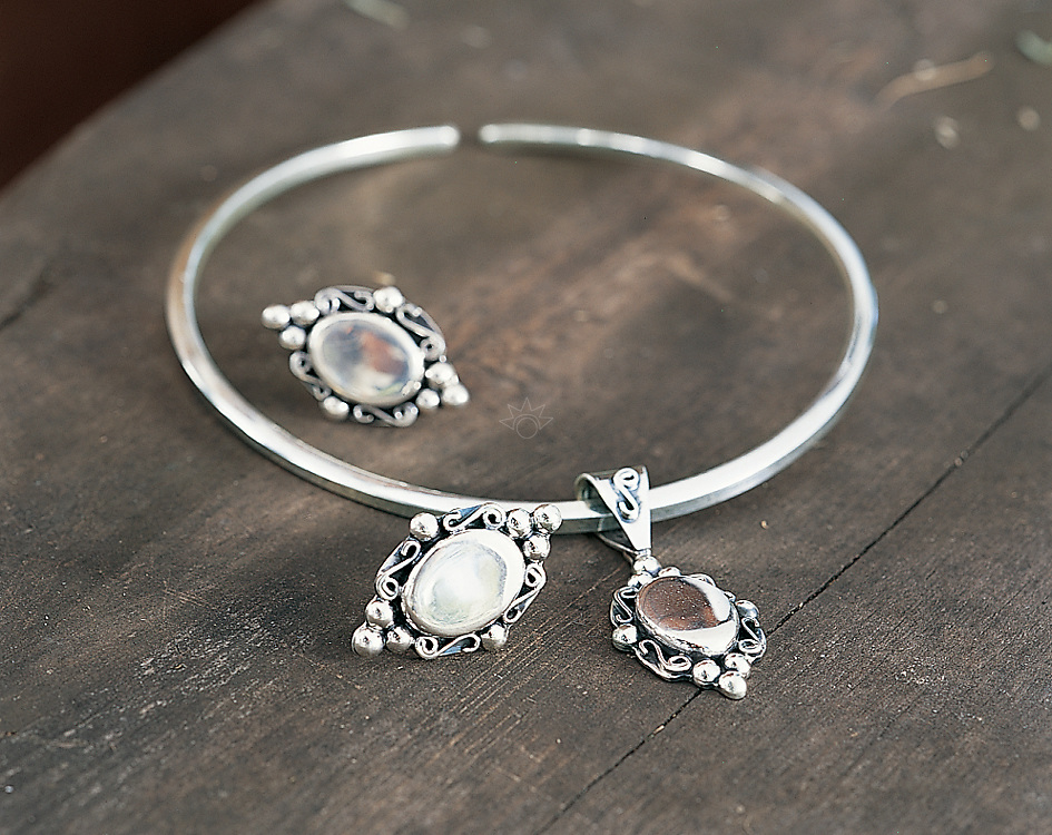 Photograph of a set of silver jewelry shot on a rustic bench for Charles Keath.