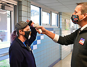Karla Chapman of Belleville (left) tips her hat up so election judge Scott Way can take her temperature as she enters Douglas School in Belleville to vote on Tuesday, November 3, 2020.  <br /> Photo by Tim Vizer