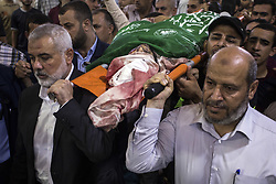 July 26, 2018 - Gaza, Gaza Strip - Hamas Chief Ismail Haniyeh (L) carries the body of Palestinian Hamas militant Mohammad Al-Areer who was killed in Israeli tank fire. The military wing of Gaza's rulers Hamas have vowed revenge after Israeli strikes that killed three members of the group in the latest flare-up of violence. Israel said the artillery fire late Wednesday was in retaliation for shots fired at troops along the border. (Credit Image: © Mahmoud Issa/SOPA Images via ZUMA Wire)