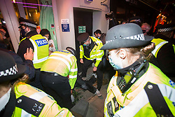 © Licensed to London News Pictures. 04/11/2020. London, UK. A man is being arrested while members of the public enjoying night out in Soho, central London. Ahead of a second national lockdown tomorrow. Strict measures are due to be re-introduced in an attempt to fight a second wave of the COVID-19 strain of Coronavirus. Photo credit: Marcin Nowak/LNP