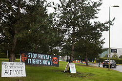 Farnborough, UK. 2nd October, 2021. A banner and signs are displayed by Extinction Rebellion climate activists outside an entrance to Farnborough Airport. Activists blocked three entrances to the private airport to highlight elevated carbon dioxide levels produced by super-rich passengers using private jets and 'greenwashing' by the airport in announcing a switch to sustainable aviation fuel (SAF).
