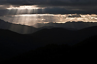 crepuscular rays formed by light through the clouds above the Gifford Pinchot National Forest in the Cascade Mountain Range in Washington state, USA