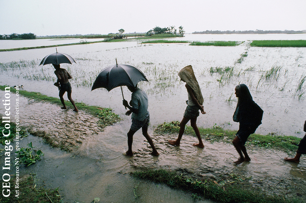 Refugees cross a flooded field during monsoon season.